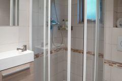 Badkamer met douche en toilet en wastafel