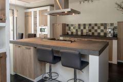 Keuken met kookeiland en 2-persoons bar.  Links van kookeiland is nog een 4-persoons bar.